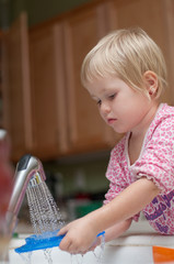 3 years old girl washing the dishes