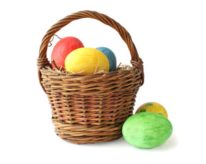 Painted Easter eggs in basket on white background