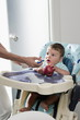 Young woman's hand feeding baby boy in high chair holding an apple