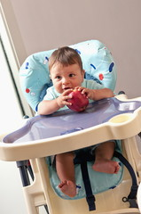 Baby boy in high chair holding an apple