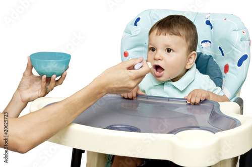 Young woman's hands feeding baby boy in high chair