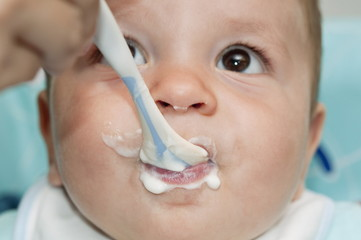 Closeup of baby boy's face with with spoon and food around his mouth