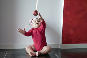 Baby boy sitting on floor reaching for Christmas ball
