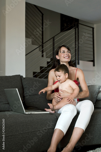 Young woman with baby at laptop computer