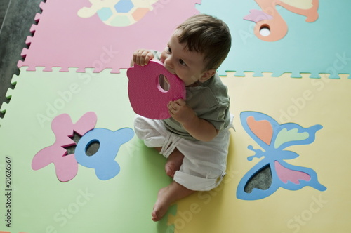 Baby boy chewing on play mat