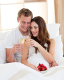 Cheerful couple drinking champagne with strawberries lying in be