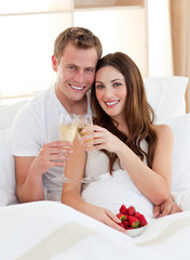 Enamoured couple drinking champagne with strawberries lying in b