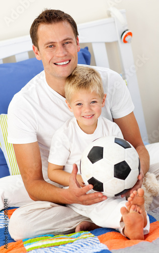 Close-up of a little boy and his father playing with a soccer ba