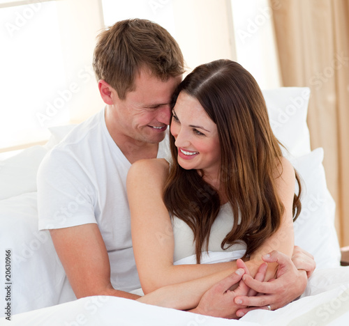 Romantic lovers embracing lying in bed