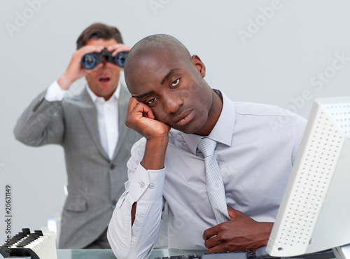 Ethnic businessman getting bored and his manager looking through