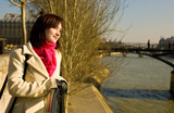 Beautiful woman in Paris on the Seine embankment near the pedest poster