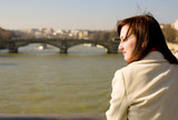 Beautiful woman in Paris on the Seine embankment, contemplating poster