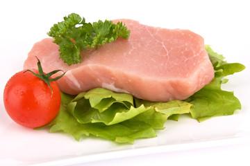 Stück rohes Fleisch mit Salat und Tomate isoliert