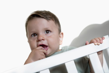 Baby boy in crib with finger in mouth
