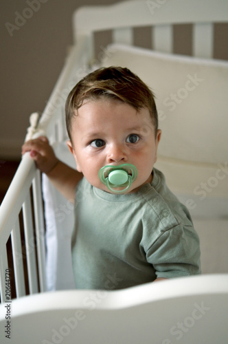 Baby boy in crib with pacifier