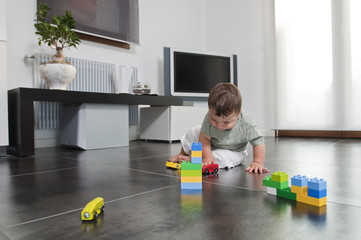 Baby boy playing with toys in living room