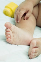 Closeup of baby's feet and hand