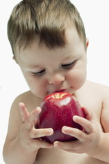 Baby boy eating an apple