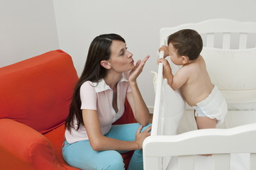 Young woman on arm chair blowing kiss at baby boy in crib