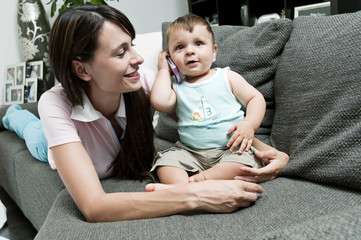 Young woman with baby on mobile phone on couch