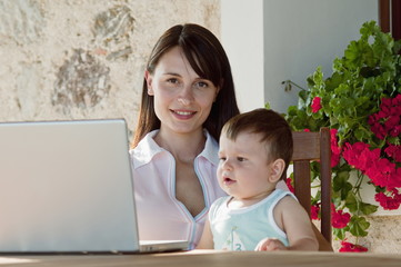 Young woman with baby and laptop computer