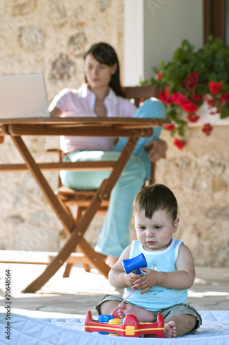 Baby playing with toy and young woman at laptop computer