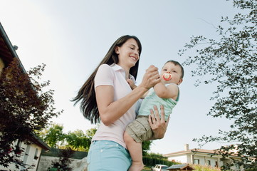 Young woman dancing in garden with baby boy