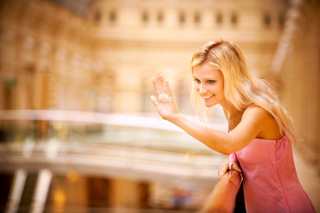 Young woman waves hand