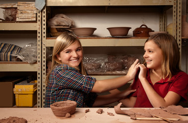 Two happy girls in clay studio