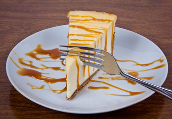 Cheesecake Drizzled With Caramel on a White Plate