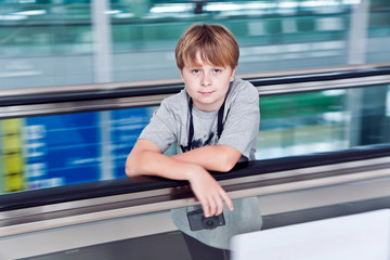 boy in  departure hall  in the Airport  on a moving staircase