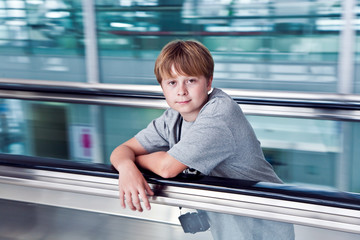 boy in departure hall  in the new Airport  on a moving staircase