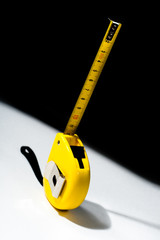 Tape measure over black white background
