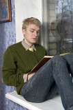 young blond man sitting and reading the book on window-sill poster