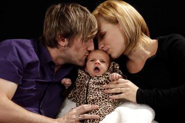 Eltern küssen ihr Baby