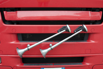 Detail of some air horns near a red truck's radiator