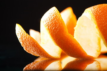 Spiral orange peel reflecting on black background.