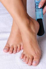 woman scrubbing her feet using the pedicure brush