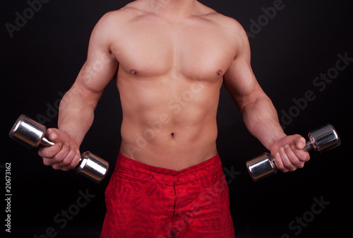muscular body and dumbbells