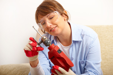 Young woman changing drill bit
