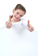 Ein Mädchen zeigt Daumen nach oben. Sample text.