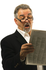 Businessman reads newspaper with a look of shock in his face