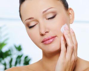 Woman applying  moisturizer cream on her cheek