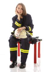Junge Feuerwehrfrau in Uniform, erschöpft