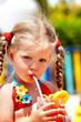 Child girl in  red bikini drink orange juice.