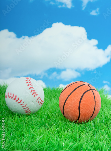 an orange basketballand a white baseball on a green lawn against
