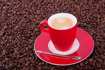 a red cup and saucer with coffee and a spoon  in the middle of t