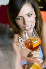 Young woman with a glass of orange wine and young man