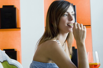 Young woman sitting with a glass of orange wine eating potato chips
