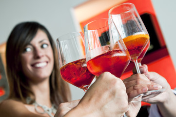 Closeup of young woman's face and other people's hands holding wine glasses and toasting